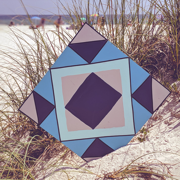 2021 Gulf Coast Quilt Trail as a part of the 2021 Foo Foo Fest. Pictured is a hand-painted quilt square, propped up on the beach in the sea oats.